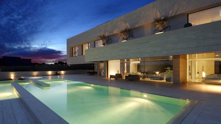 Fachada minimalista posterior con la piscina como espejo de agua.